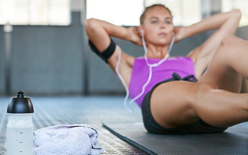 Mulher de camisa rosa, realiza exercício abdominal no chão. Ao seu lado, estão dois itens: uma garrafa de beber água e uma toalha