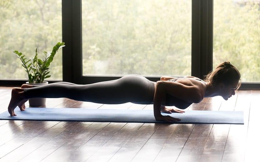 Mulher se posiciona com os braços e pés apoiados no chão, se estendendo em uma sala de chão de madeira. Ela realiza exercícios com as respostas do mitos sobre as atividades físicas