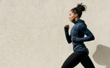 Uma moça corre. Ao seu fundo, uma parede beje. A atleta se beneficia das respostas obtidas nos mitos sobre atividades físicas