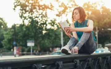 Garota sentada ao ar livre lê um livro e coloca em prática os ensinamentos sobre a importância da atividade física para os estudos