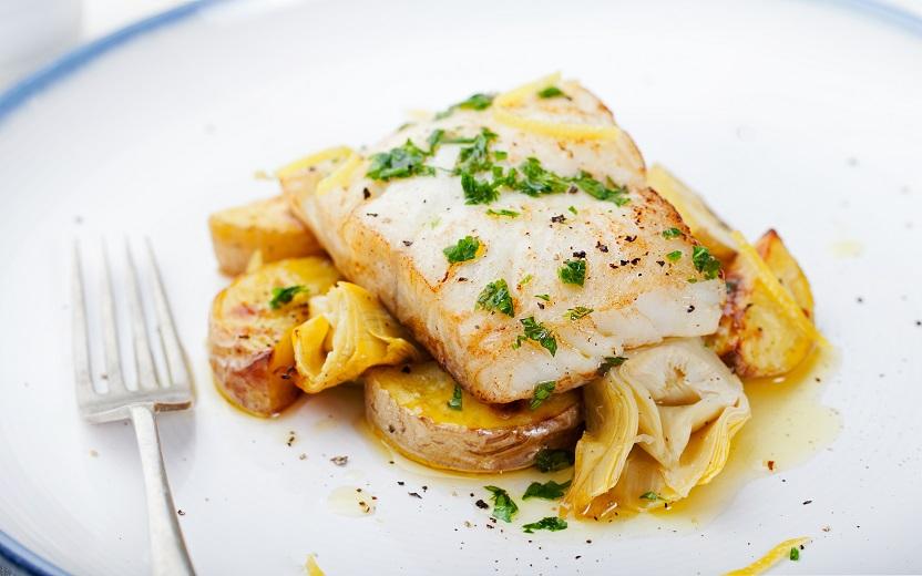 Bacalhau com pedaços de alcachofras e batatas com um garfo ao lado. Todos eles encontram-se acima de um prato branco. Unir vegetais com a espécie de peixe pode ser uma forma de receita saudável para o bacalhau