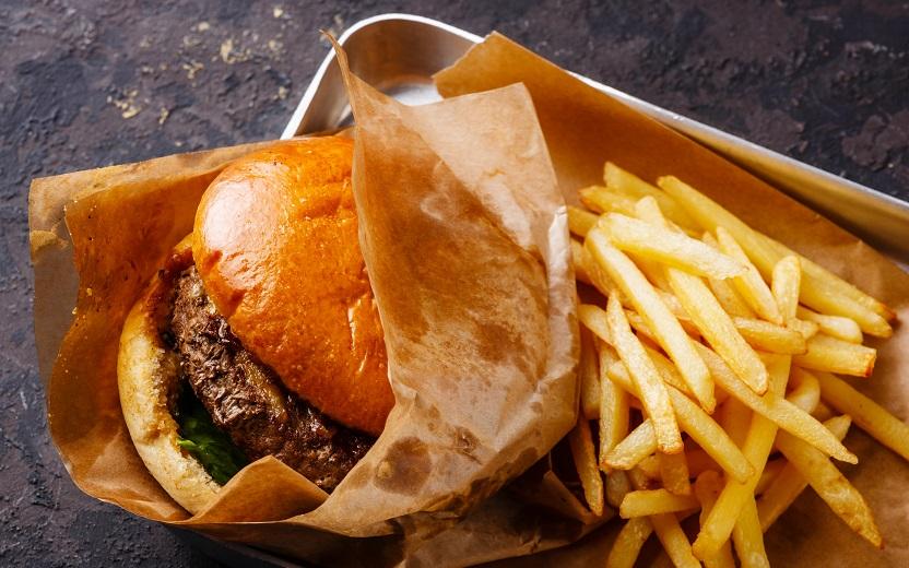 Pão com hambúrguer e batata fritas em embalagens. Nutrientes são ricos em gorduras e fazem parte da categoria comfort food